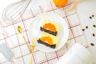 テーブルの上に乗っているみかんムースケーキの写真・画像素材[3920825]