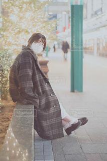 マスクをつけてコートを羽織ってクリスマスツリーをバックにこっちを見る女性の写真・画像素材[3968782]