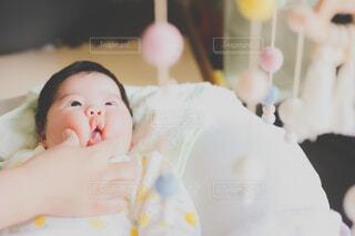 メリーを見ながらほっぺで遊ばれる赤ちゃんの写真・画像素材[3971895]