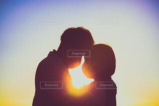 夕日の前で見つめあっているカップルの写真・画像素材[3973368]