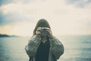 浜辺でカメラでシャッターを切っている女性の写真・画像素材[3973370]