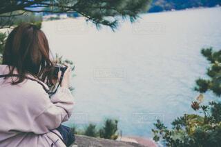 座りながら海をカメラで撮る女性の後ろ姿の写真・画像素材[3975944]