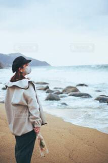 花束を持って浜辺に立つ人の写真・画像素材[4219994]