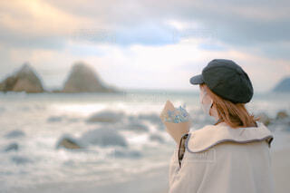 帽子をかぶって花束を持って浜辺に立つ女性の写真・画像素材[4219995]