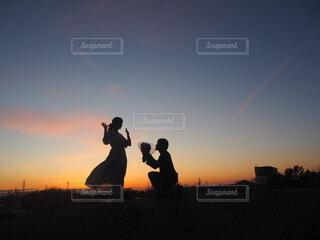 夕日の前に立っている人の写真・画像素材[4060297]