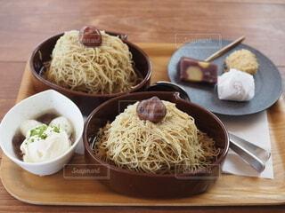 木製のテーブルの上に座っている食べ物のボウルの写真・画像素材[3863455]