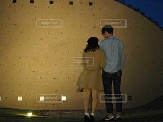 壁の前に立っている男女の写真・画像素材[3905868]