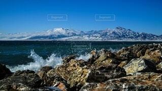 背景に山のある水の体の写真・画像素材[3855901]