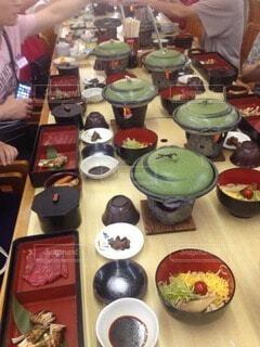 食べ物でいっぱいのテーブルに座っている人々のグループの写真・画像素材[3858664]