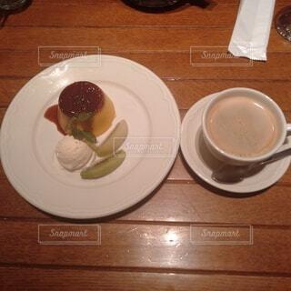 食べ物の皿と一杯のコーヒーを木製のテーブルに置いての写真・画像素材[3874077]