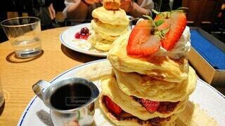 お皿に乗った4段パンケーキとメープルシロップの写真・画像素材[3878685]