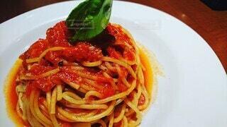 白いお皿に盛り付けられたトマトパスタの写真・画像素材[3884341]