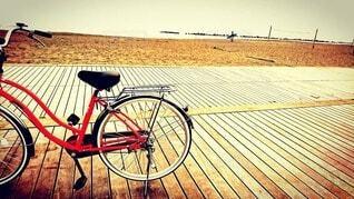 ビーチに停めたオレンジ色の自転車の写真・画像素材[3884378]