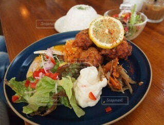 木製のテーブルの上に食べ物の皿の写真・画像素材[3931678]