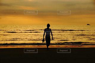 水の体の上に日没の前に立って - No.1017767