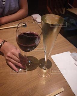 ワイングラスを持つテーブルに座っている女性の写真・画像素材[1415110]