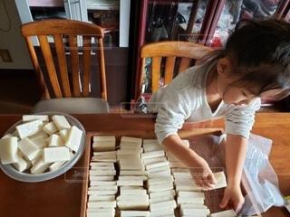 お正月の切り餅のお手伝いをする子どもの写真・画像素材[4049208]