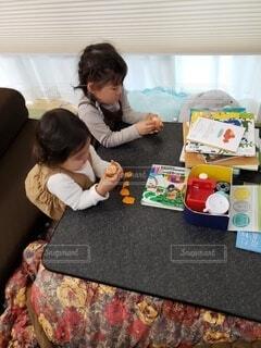 こたつでみかんを食べている子ども達の写真・画像素材[4091957]