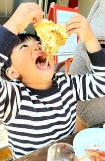 ピザを食べている少年の写真・画像素材[4099105]