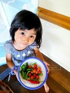庭の夏野菜が入ったザルを持つ3才の女の子の写真・画像素材[4666569]