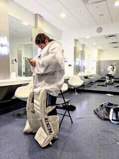 女子ホッケーのゴールテンダー、ロッカールームで片手に携帯電話。の写真・画像素材[3867149]