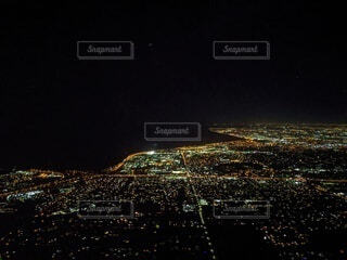 夜の海岸線、上半分は海、下半分は街の写真・画像素材[3905556]