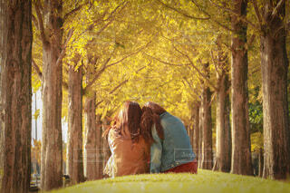 秋の並木道に座るふたりの写真・画像素材[3926263]