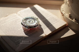 窓辺に置かれた洋書とコンパクトの写真・画像素材[3974228]