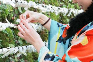 初詣でおみくじを結ぶ女性の写真・画像素材[4034214]