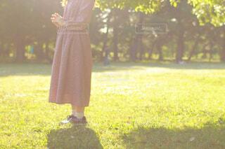 芝生に佇むワンピースの女性の写真・画像素材[4409077]