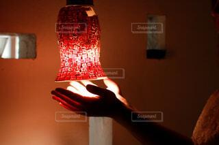 赤い照明に手をかざす女性の写真・画像素材[4564420]