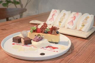 木製テーブルの上のケーキとフルーツサンドの写真・画像素材[4771513]