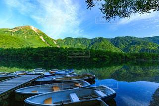 山を背景にした水域のボートの写真・画像素材[3938321]