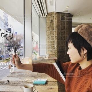 窓際の冬服の女性の写真・画像素材[3937861]
