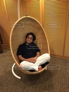 籐の吊り下げ椅子で寛ぐ人の写真・画像素材[3990106]