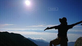 山の上で絶景を身体いっぱいで感じる友人の写真・画像素材[3917296]