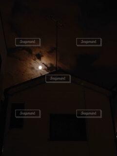 民家の後ろで輝くお月さまの写真・画像素材[3933202]