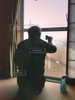 和室の窓拭きを念入りにする父の写真・画像素材[4011008]