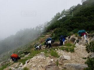 岩山を必死で登る人々の写真・画像素材[4940561]