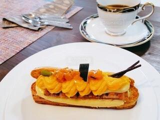 コーヒーとエクレアでティータイムの写真・画像素材[3903998]
