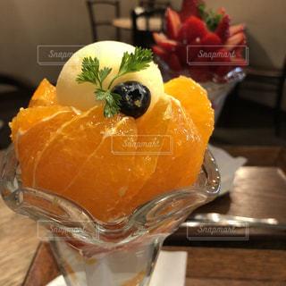 テーブルの上のオレンジ ジュースのガラスの写真・画像素材[1354836]