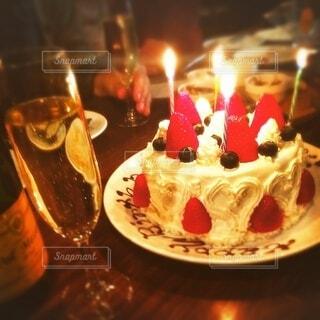 ろうそくに火が灯っているケーキとシャンパングラスのアップの写真・画像素材[3956793]