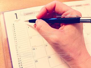 ペンを持ってスケジュールを書く手の写真・画像素材[3998111]