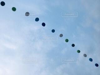 曇った青空で凧を飛ばす人々のグループの写真・画像素材[3931130]