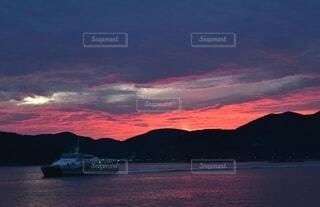 夕焼けの中帰島する船の写真・画像素材[3933844]