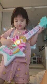 子ども,屋内,少女,遊ぶ,人物,壁,人,可愛い,楽器,幼児,若い,グッズ,オモチャ,ノリノリ,人間の顔,ギターのオモチャ,将来はミュージシャン?!