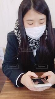 座ってスマホを見ている女性の写真・画像素材[3990529]