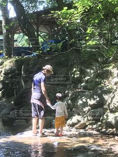木の隣に立っている男の写真・画像素材[3955389]