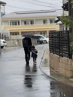 傘を持って通りを歩いている人々のグループの写真・画像素材[3955398]