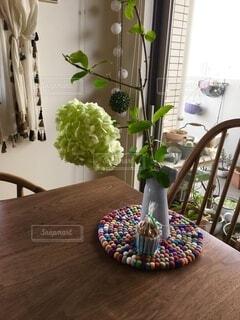 木製のテーブルの上の花瓶とお菓子の写真・画像素材[3975894]